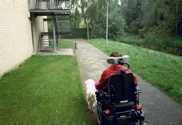 Beau geleidt de elektrische rolstoel, bezien vanaf de achterzijde.