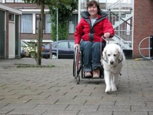 Beau geleidt Petra bij handbewogen rolstoel.